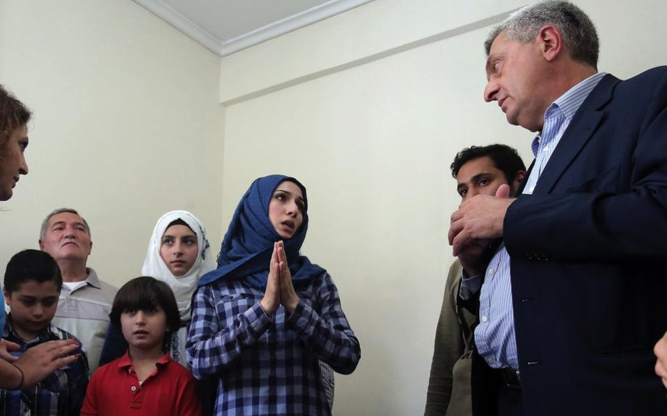 United Nations High Commissioner for Refugees Filippo Grandi (r) talks with a Syrian refugee family living in an apartment in Athens, Wednesday.