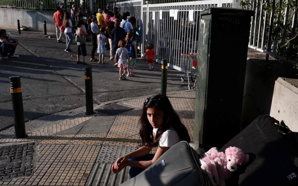 A refugee girl sits waits outside the asylum service in Athens along with other migrants and refugees for their hearings on Monday.  Some 58,453 officially registered  refugees and migrants are stranded in Greece since the closure of the borders, with many of them seeking asylum in Greece.
