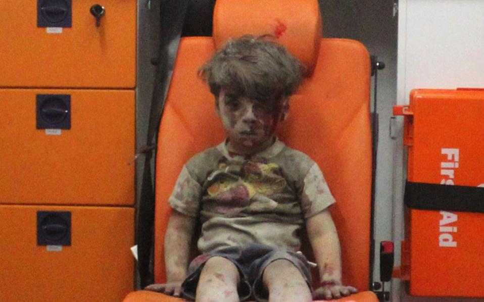 Five-year-old Omran Daqneesh, with bloodied face, sits inside an ambulance after he was rescued following an airstrike in the rebel-held al-Qaterji neighborhood of Aleppo, Syria, Wednesday.