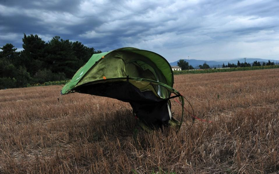 An abandoned tent is blown by the wind at the former site of a makeshift refugee camp near the Greek village of Idomeni.