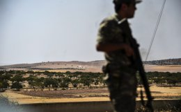 A Turkish soldier stands guard in the Turkish Syrian border city of Karkamis in the southern region of Gaziantep, on Wednesday as Turkish army tanks and pro-Ankara Syrian opposition fighter trucks positioned two kilometres west from the Syrian Turkish border town of Jarabulus, prepare to move position.