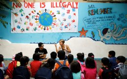 British volunteer primary school teacher Helen Brannigan (c) speaks to refugee children before class at the volunteer-run Refugee Education Chios school on the island of Chios.