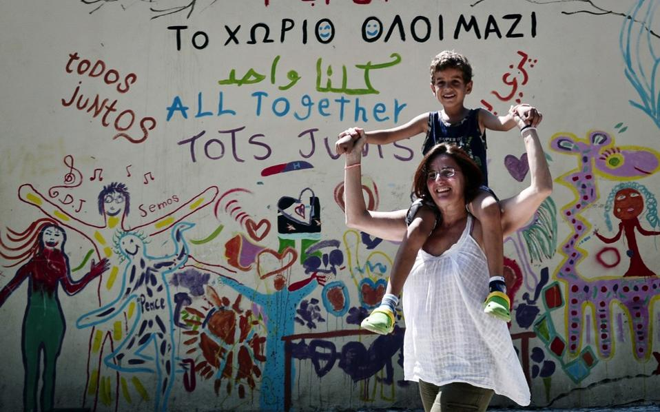 Activist Efi Latsoudi plays with  a refugee boy at the 'Village All together' or PIKPA village on the island of Lesvos on August 31.