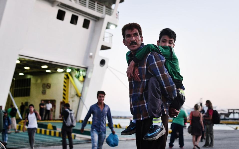 man_child_boat_migrants_web