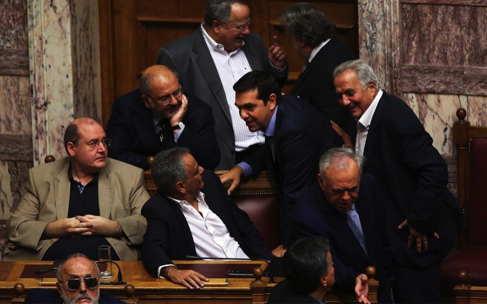 Greek Prime Minister Alexis Tsipras (c) talks with ministers during the debate on the omnibus bill for prior actions demanded by Greece's creditors, in the Greek Parliament in Athens, Tuesday.