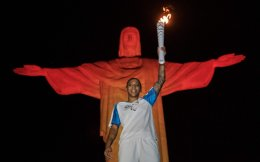 Brazilian judoka Rafaela Silva, who won the gold medal during the Rio 2016 Olympic Games, holds up the torch for the Rio 2016 Paralympic Games in front of the statue of Christ the Redeemer atop Mount Corcovado in Rio de Janeiro, on Tuesday evening.