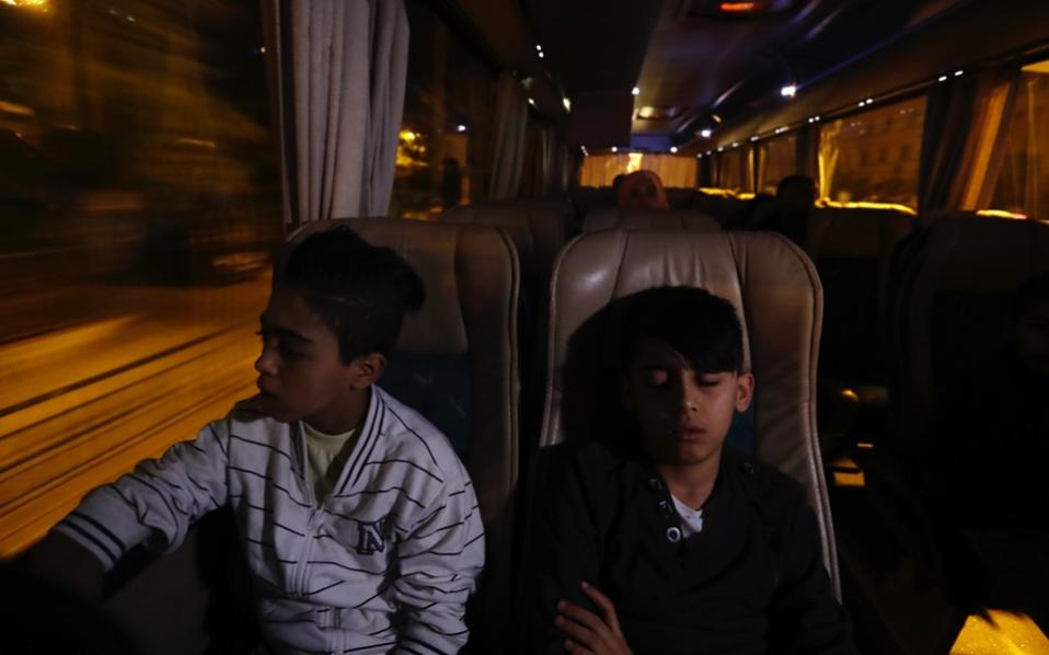 A boy looks the coach route while another one sleeps as they head to Athens International Airport for a flight to Madrid on Monday.