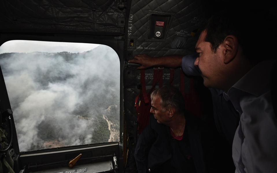 A handout picture provided by the Greek Prime Minister's Press Office Monday shows Greek Prime Minister Alexis Tsipras on a military helicopter, watching a forest fire that burns on the island of Thasos, in northern Greece.
