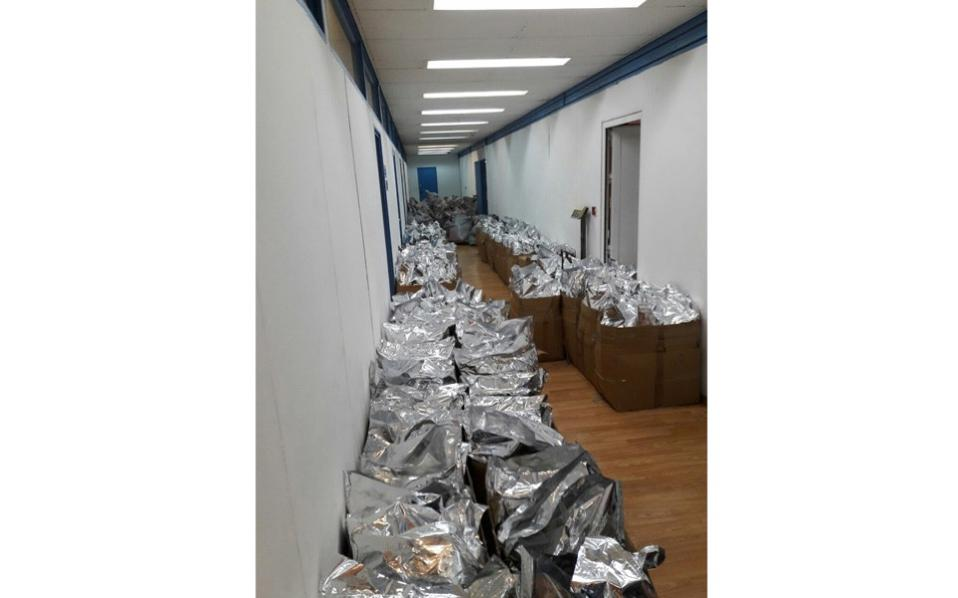 This police handout photo shows hundreds of packages of cannabis stacked in a hallway at police HQ.
