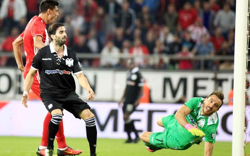 Oscar Cardozo celebrates Olympiakos's winning goal past PAOK keeper Panayiotis Glykos.