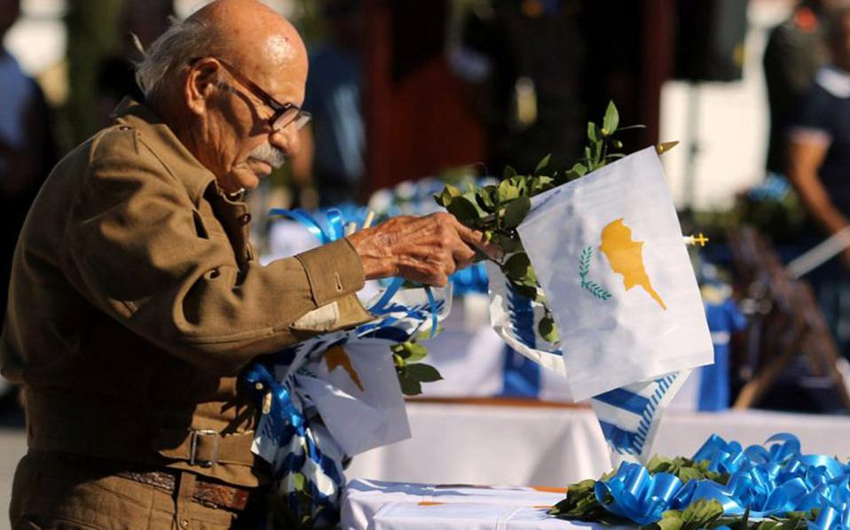 A man leaves Greek and Cypriot flags on caskets of Greek soldiers, whose remains were recently discovered in the wreckage of a Greek military aircraft shot down by friendly fire in 1974, at the Tymvos Macedonitissas military cemetery in Nicosia, on Tuesday.