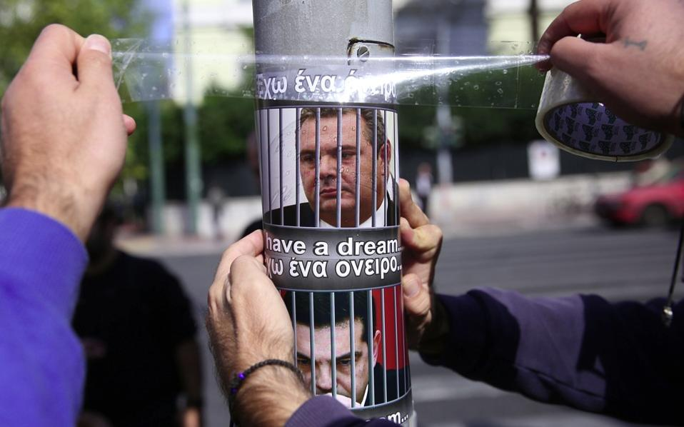 Staff of private television channels sticking flyers depicting PM Alexis Tsipras and his coalition partner Panos Kammenos outside Parliament on Wednesday.