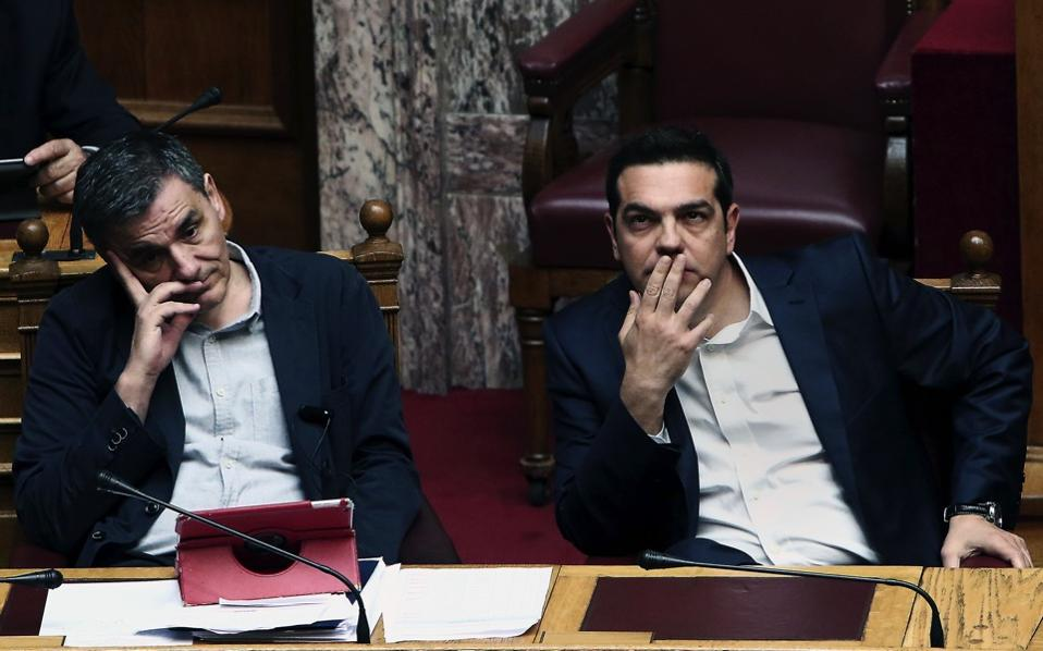 Greek Prime Minister Alexis Tsipras (r) and Greek Finance Minister Euclid Tsakalotos (l) attend a parliamentary session in Athens, May 22, ahead of a vote on fresh cuts and tax hikes. After waves of protests over a string of unpopular reforms, lawmakers from the ruling leftist party approved a fresh round of austerity incorporating 1.8 billion euros in tax increases on May 22. [Angelos Tzortzinis/AFP]