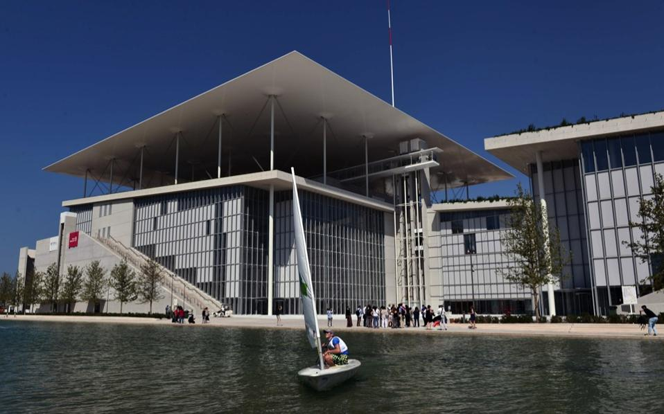 A man sails a laser in front of the newly built Athens National Opera (l) and Library buildings at the Stavros Niarchos Cultural Center in the southern Athens suburb of Faliro, June 24. The 1,400-seat opera, library and adjoining park designed by Italian architect Renzo Piano cost nearly 600 million euros ($680 million) and took eight years to design and build. The Stavros Niarchos Cultural Center, expected to fully open in mid-2017, occupies 20 hectares (50 acres) overall. [Louisa Gouliamaki/AFP]