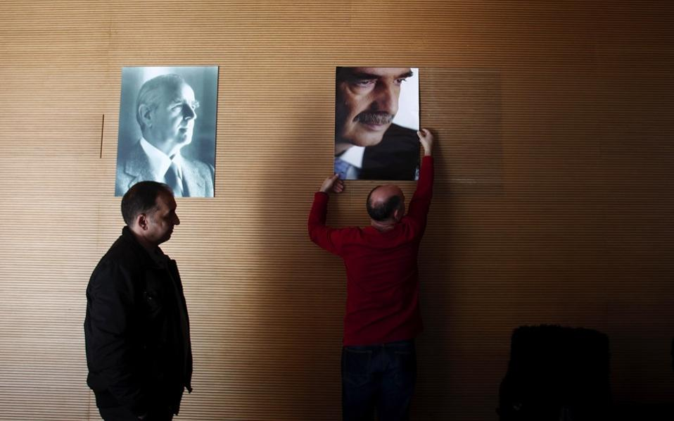 An employee of the New Democracy party reaches up to remove a portrait of interim party leader Vangelis Meimarakis from a wall at the party headquarters in Athens, January 11. Kyriakos Mitsotakis was elected president of the conservative party in runoff elections on January 10, defeating Meimarakis, who had served as interim party leader over the summer after former prime minister Antonis Samaras stepped down. [Alexandros Vlachos/EPA]