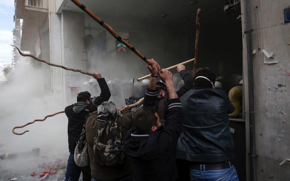 Farmers clash with riot police during a protest outside the Ministry of Agriculture in Athens, February 12. Farmers from across Greece gathered in the capital for a two-day protest against the government and its plans to impose new tax hikes and pension cuts. [Thanassis Stavrakis/AP]
