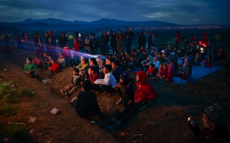 Children watch an animated movie in a field at the northern Greek border station of Idomeni, March 5. The Idomeni border crossing in the Greek region of Central Macedonia became a bottleneck where thousands of migrants were trapped as they tried to find refuge and a better life in Europe. [Vadim Ghirda/AP]