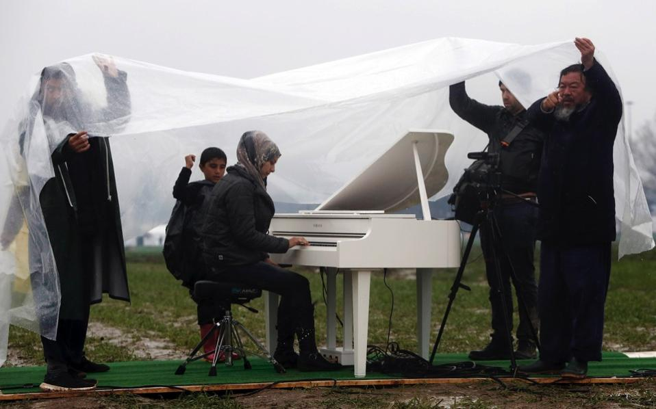 Chinese contemporary artist Ai Weiwei protects himself and others from the rain as Nour Al Khizam, from the city of Deirez Zor in Syria, plays the piano during a performing at a refugee camp near Idomeni in northern Greece, March 12. [Yannis Kolesidis/EPA]