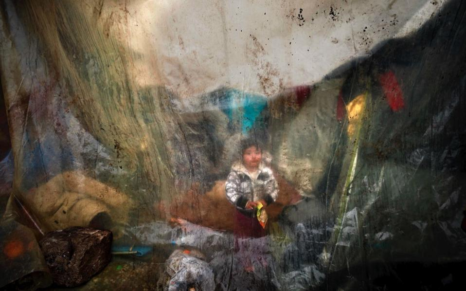 A migrant child sits behind plastic sheets covering tents as it rains in a makeshift camp at the northern Greek border post of Idomeni, northern Greece, March 15. [Vadim Ghirda/AP]