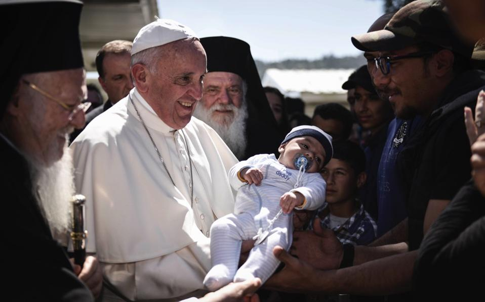 Pope Francis, leader of the Catholic Church, holds a baby during his visit to the Moria hot spot for migrants and refugees near Mytilene on the Greek island of Lesvos, April 16. The pontiff challenged leaders to respond to migrants 'in a way worthy of our common humanity' and pointedly called for Europe to remember its roots as 'the homeland of human rights.' He drove the point home by returning to Rome with a group of Syrians who were among the thousands stranded in Greece as a result of the decision by many European Union member-states to bar new arrivals. [Andrea Bonetti/Prime Minister's Office/AFP]