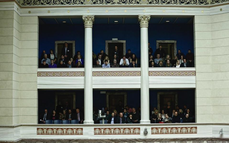 People watch a parliamentary session prior to a budget vote in Athens, on Saturday.