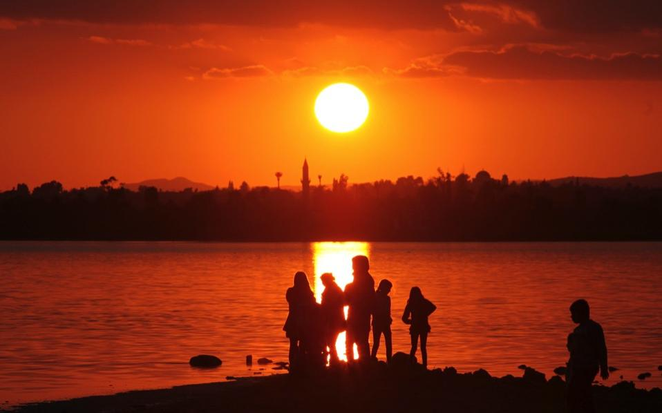 People watch the sun set over a salt lake in Larnaca.