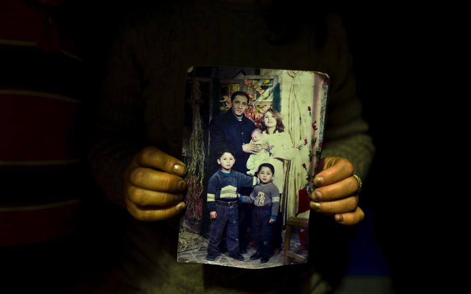 Fidan Kiru, 31, a Syrian refugee from Afrin, holds a photograph taken in 2004 showing herself and her husband Mohyeddin, when he was 27-year-old, and her sons, younger to older, Avindar, 8 months, Khalid, 4 and Levant, 6, at her tent in Kalochori refugee camp on the outskirts of the northern Greek city of Thessaloniki. 'This is the only group family picture we have, my husband is currently in Germany and I hope they will allow me to join him,' Fidan said.