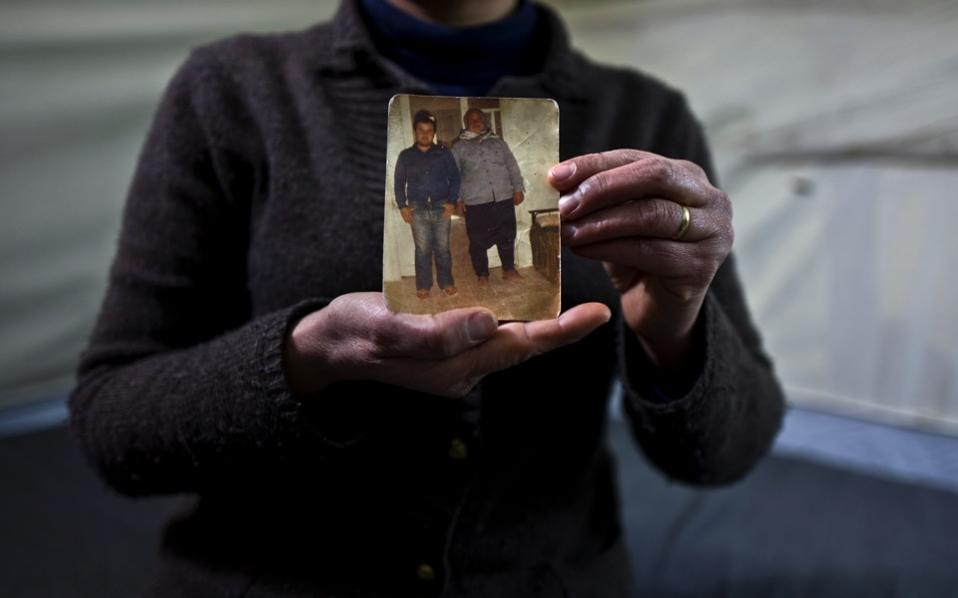 Habeeba Waqas, 40, a Syrian refugee from Aleppo, holds a photograph showing her husband Mohammed and her father in law Suliman at her tent in Frakapor refugee camp on the outskirts of the northern Greek city of Thessaloniki. 'This is the only memory that I carried with me from Syria, my husband was young and handsome in this picture,' Habeeba said.