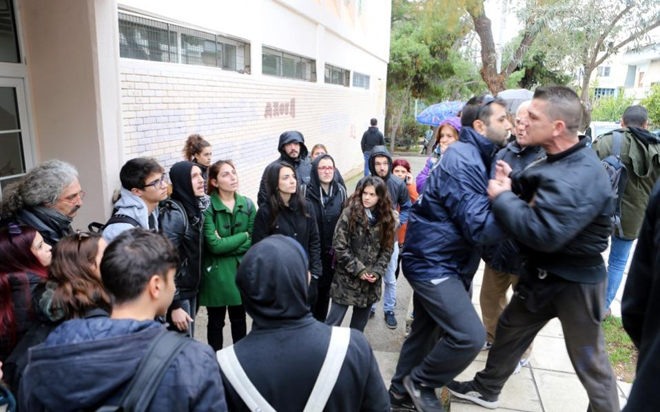 A police officer holds back a man lunging at pro-migrant activists outside a school in Keratsini, near Piraeus, on Wednesday. Some parents of pupils at the school are opposing the admission of migrant and refugee children.