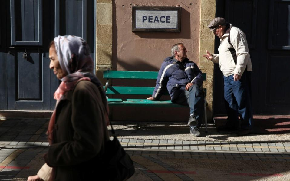 People are seen on Ledras Street next to a peace sign near the UN-controlled buffer zone in Nicosia.