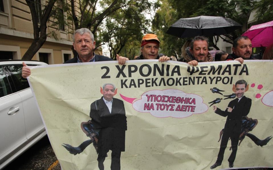 Protesting public hospital workers carry a banner with caricatures of Prime Minister Alexis Tsipras and his coalition partner Panos Kammenos with elongated noses, accusing them of lying.