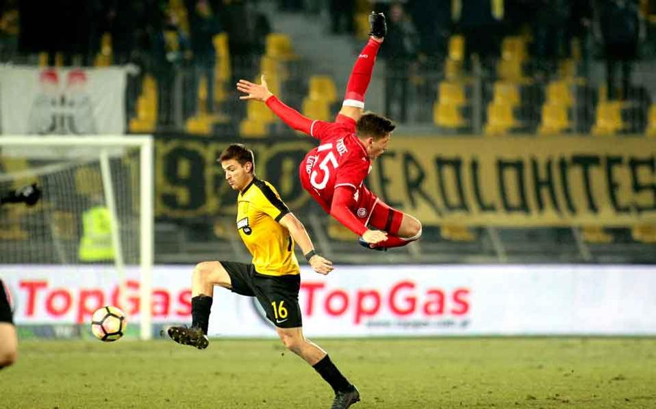 Olympiakos's Panayiotis Retsos flies during the game with Aris.