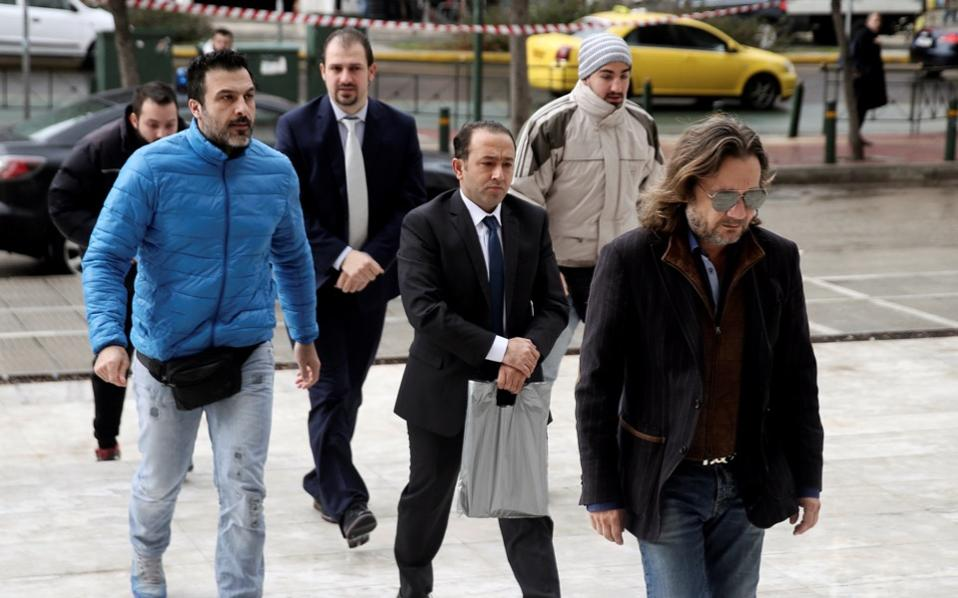 Two of the eight Turkish servicemen (center front and back), who fled to Greece in a helicopter and requested political asylum after a failed military coup against the government, are escorted by police officers as they arrive at the Supreme Court in Athens on Wednesday.