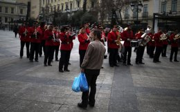 A man holds shopping bags as he watches the Big Band of the Municipality of Athens perform in central Athens, yesterday. If Greece were to return to the drachma, people's purchasing power would be drastically reduced.