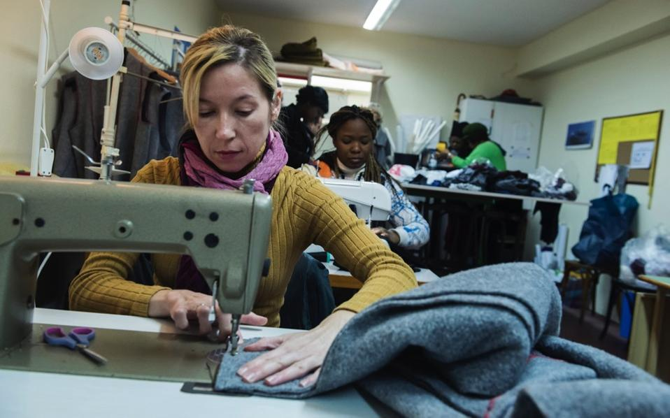 A migrant sews a blanket, at a tiny coat workshop charity called Naomi in the northern Greek city of Thessaloniki, which is working long hours to collect and wash discarded blankets and turn them into wearable coats.