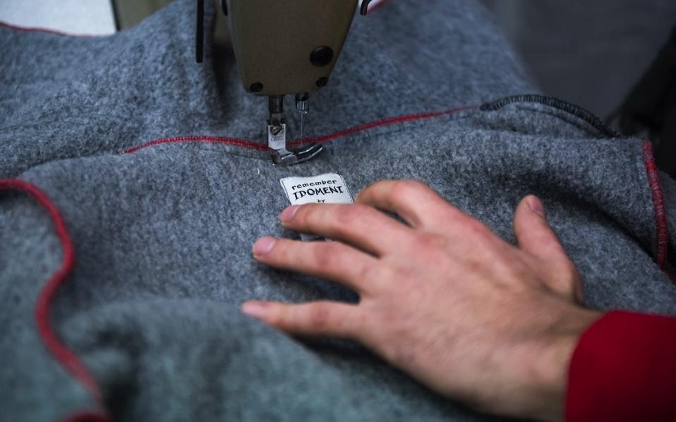 Hasan Mitwally Al Kodsy, 30, from Syria, manufactures a coat made from a blanket, at a tiny workshop charity called Naomi in the northern Greek city of Thessaloniki, which is working long hours to collect and wash discarded blankets and turn them into wearable coats.