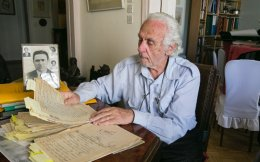 Marios Sousis studies the material he plans to use in a book on the trial against the men who robbed his family.