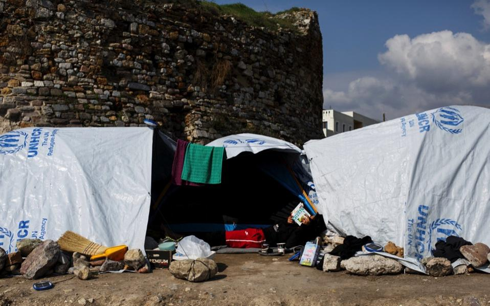 A migrant reads a book outside his tent at the Souda camp for refugees and migrants on the island of Chios, last week.