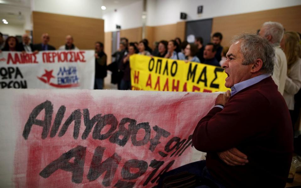 Protesters shout slogans as they block an entrance to prevent court officials from entering the courtroom and carry out an auction in Athens.