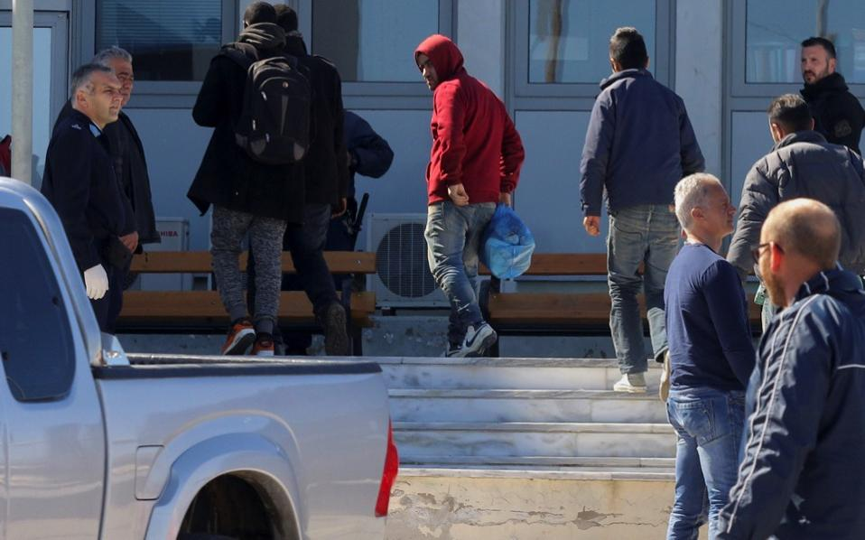 Undocumented migrants are transferred to the police headquarters after being arrested during an operation to dismantle an international smuggling ring at the city of Iraklio on the island of Crete, Friday.