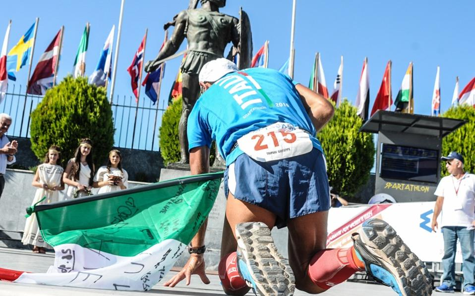 A runner drops to his knees in front of the statue of Leonidas in a file photo from last year's Spartathlon.