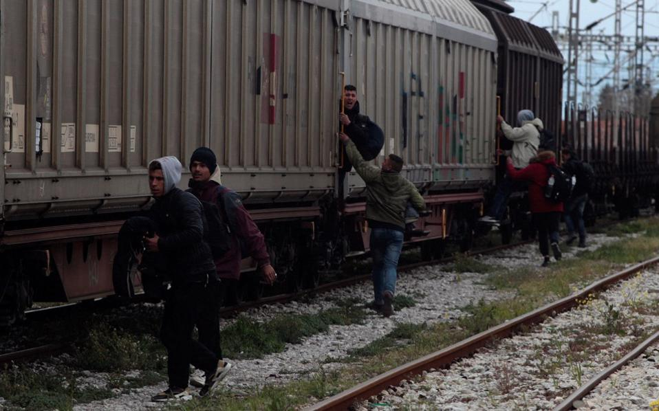 Migrants jump on a freight train in Thessaloniki in a bid to cross from Greece into the Former Yugoslav Republic of Macedonia