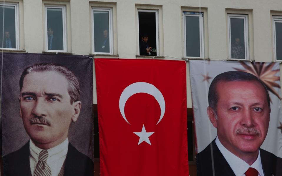 Banners showing modern Turkey's founder Mustafa Kemal Ataturk and current President Recep Tayyip Erdogan decorate a building as people watch Erdogan's speech, during a rally for the upcoming referendum, in his hometown city of Rize, in the Black Sea region, on Monday.