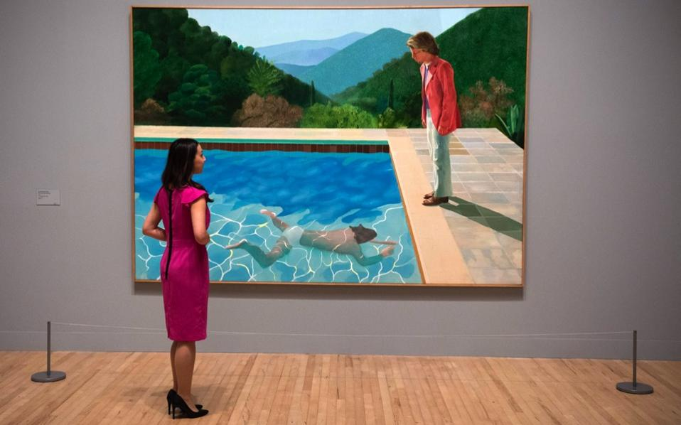 A member of staff looks at 'Portrait of an Artist (Pool with Two Figures)' by British artist David Hockney at Tate Britain.