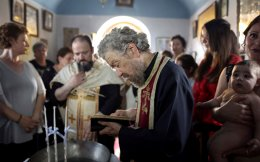 An Orthodox priest reads the gospel during the baptism of the first baby born on the islet of Thymaina after six years, with the financial support of the Aegean Team doctors, on the islet of Ayios Minas, May 12.