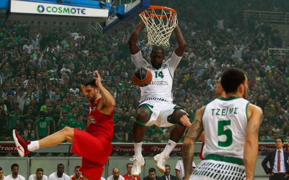 Panathinaikos's James Gist dunks the ball past Olympiakos's Costas Papanikolaou.