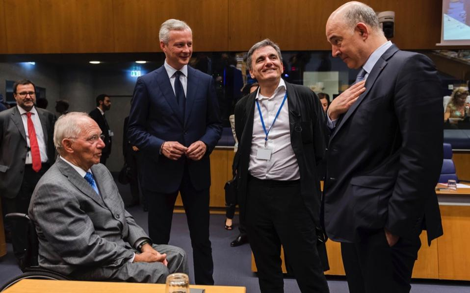 German Finance Minister Wolfgang Schaeuble, left, speaks with from right, European Commissioner for Economy Pierre Moscovici, Greek Finance Minister Euclid Tsakalotos, and French Finance Minister Bruno Le Maire during a meeting of eurogroup finance ministers at the European Council building in Luxembourg on Thursday.