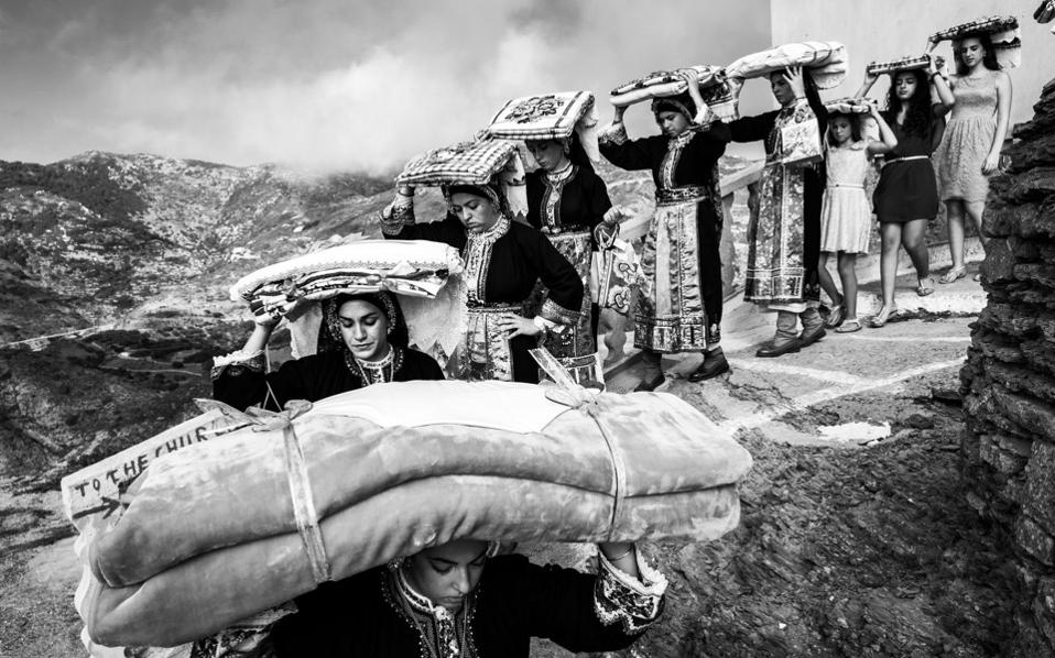 Women carry the groom's dowry to the bride's house in Olymbos in Karpathos. [Pculiar.com]