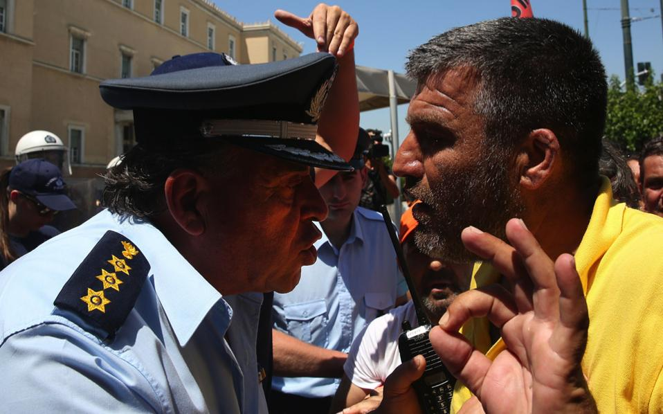 A municipal worker scuffles with police officers at the main entrance of the parliament building during a rally against job lay-offs affecting their sector, in Athens, yesterday.