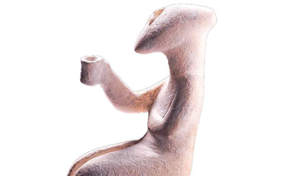 A marble figurine of a sitting man raising a cup, circa 2300-2700 BC.